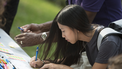 Female student drawing on paper at OMA picnic