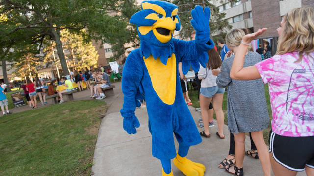 UWEC Mascot Blu high-fiving students at cookout