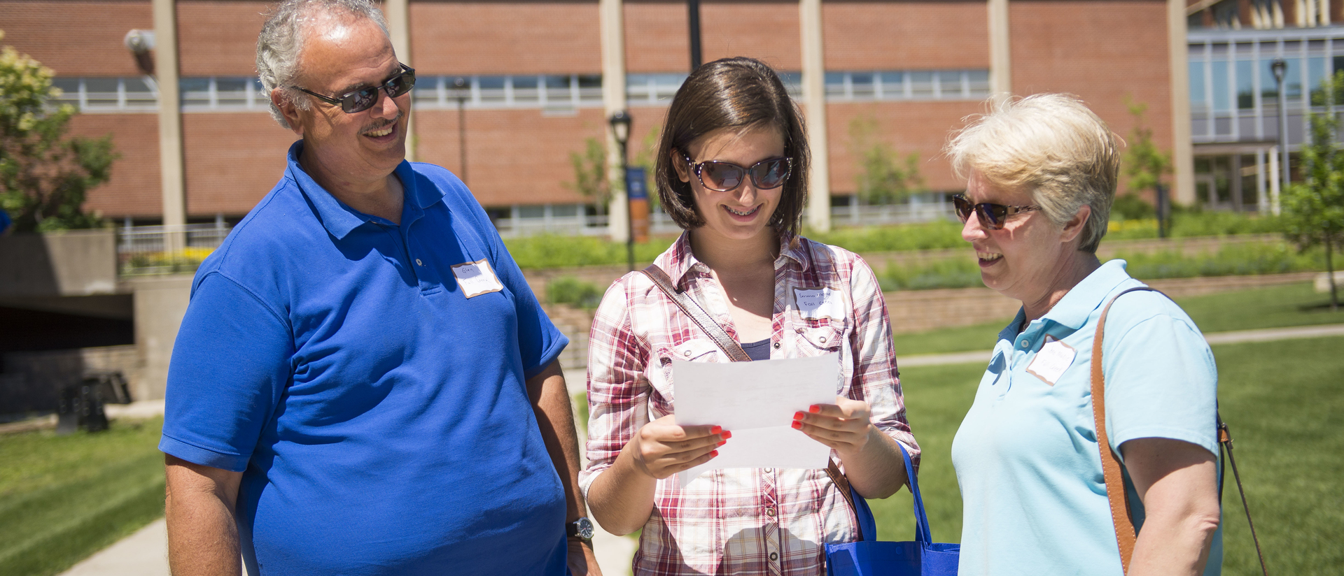 Parents and student on cmapus for orientation, outside on campus mall.