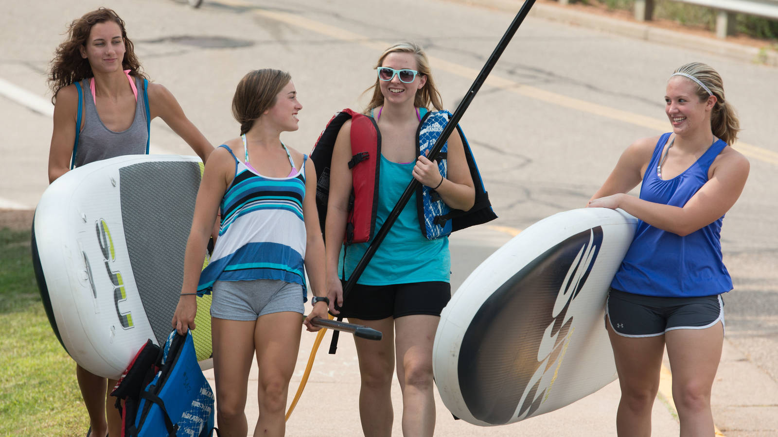 Students heading out to river float with rented paddle boards and tubes