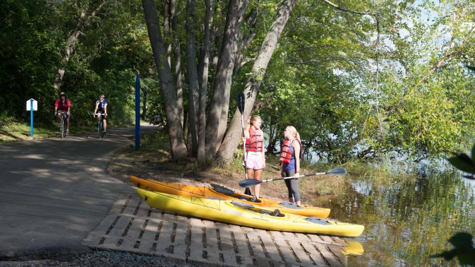 Students using rented kayaks, entering Chippewa River on the bike trail near campus.