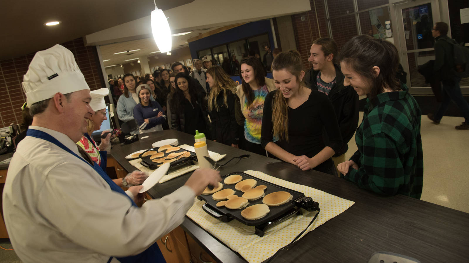 Chancellor Jim Schmidt flips pancakes for chanhungry students during finals week.