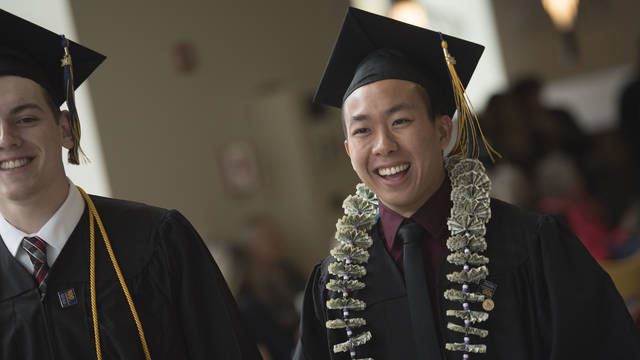 Male student on commencement day in cap and gown