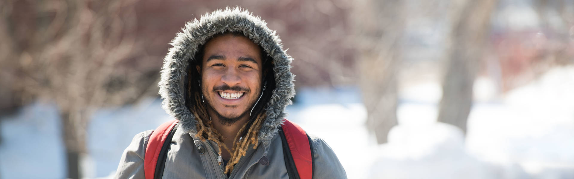 Male student on campus mall bundled up for cold weather