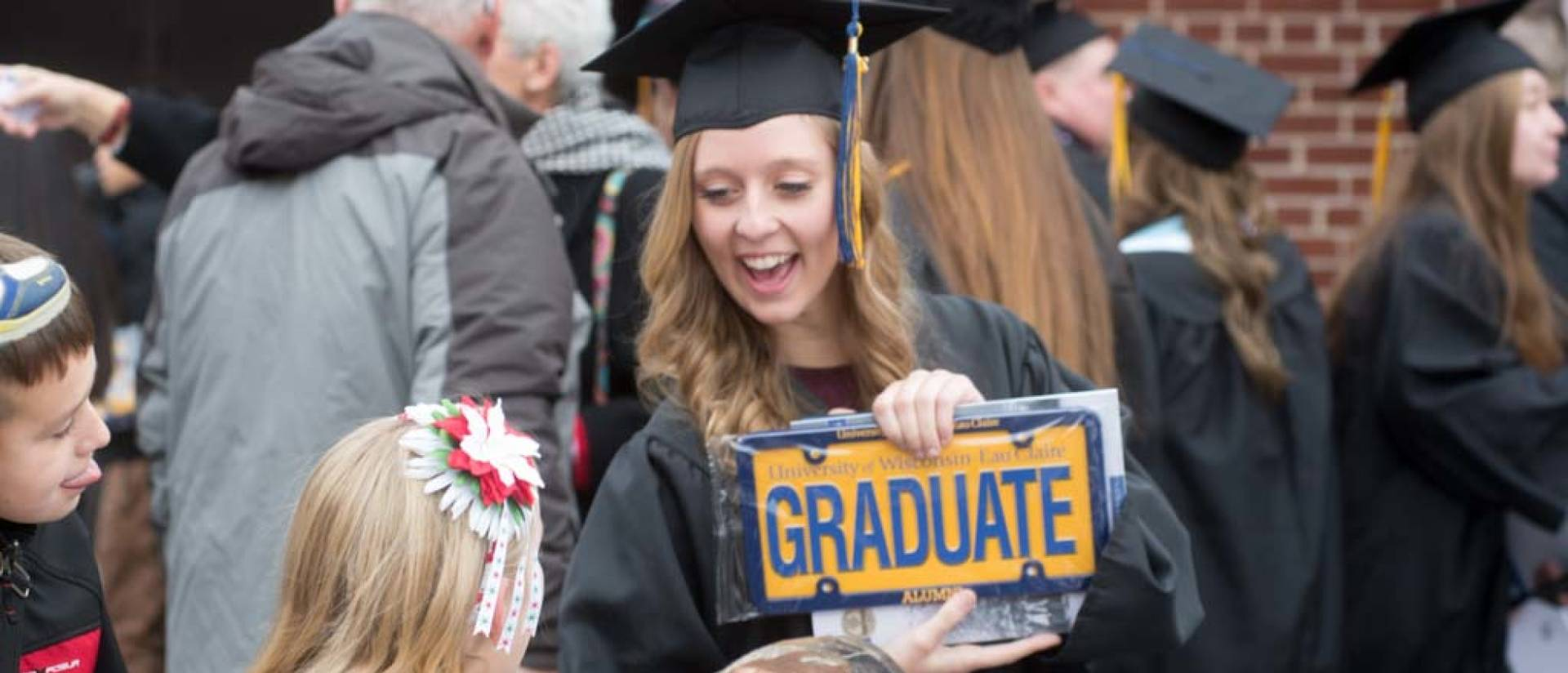 "Student outside at commencement holding license plate that says ""graduate"""