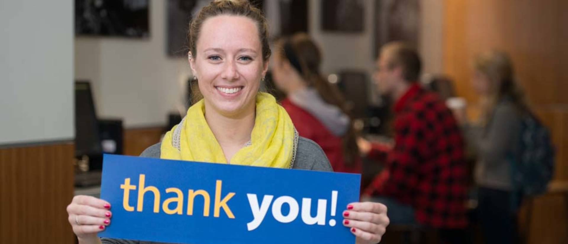 UW-Eau Claire scholarship recipient holding thank you sign.