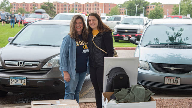 Blugold mom and student standing outside near residence hall