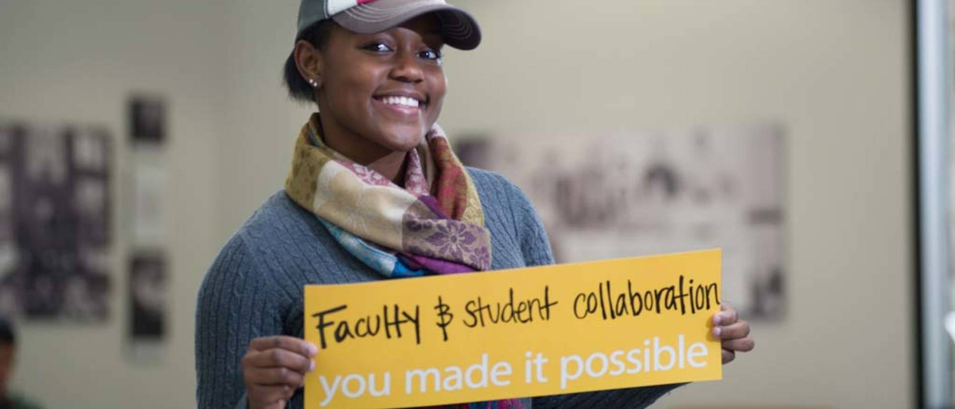 "UW-Eau Claire student holds sign that reads ""Faculty and student collaboration - you made it possible."""