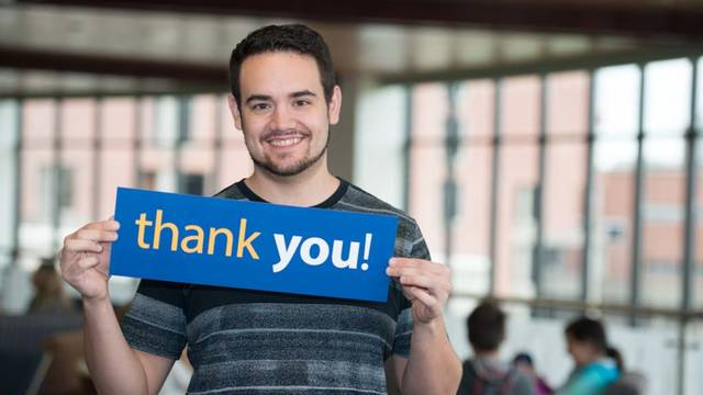 UWEC student Brendon Hernandez holds Thank You sign