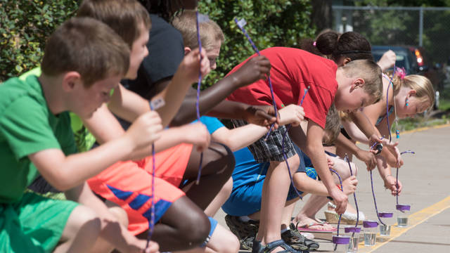 Young students working on science project outdoors at Summer Institute program put on by UW-Eau Claire's Continuing Education.