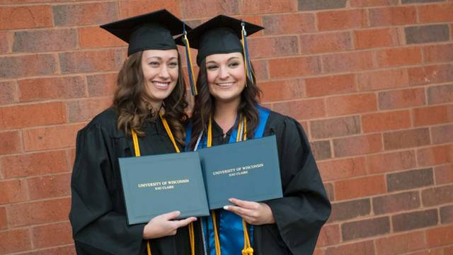 Two graduates holding their diplomas during the afternoon commencement.
