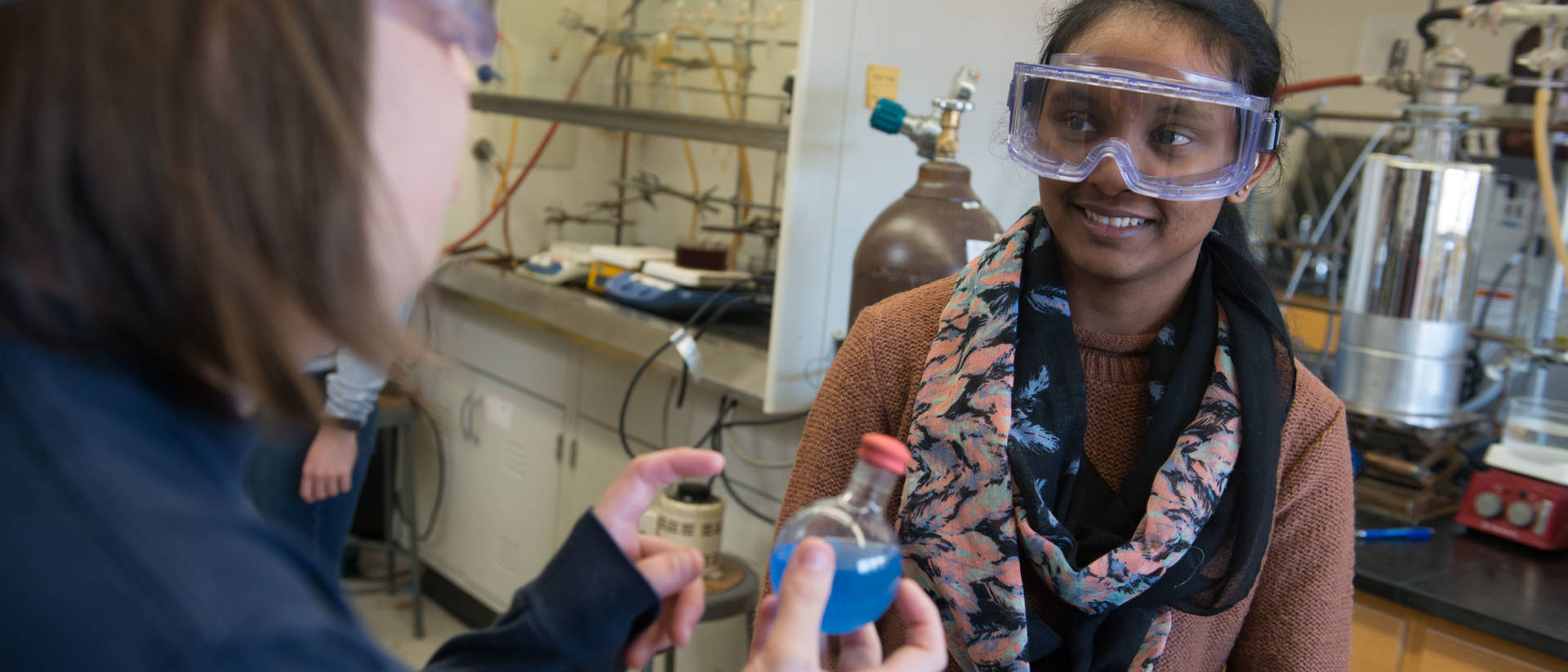 Two female students conducting research in polymers lab on campus