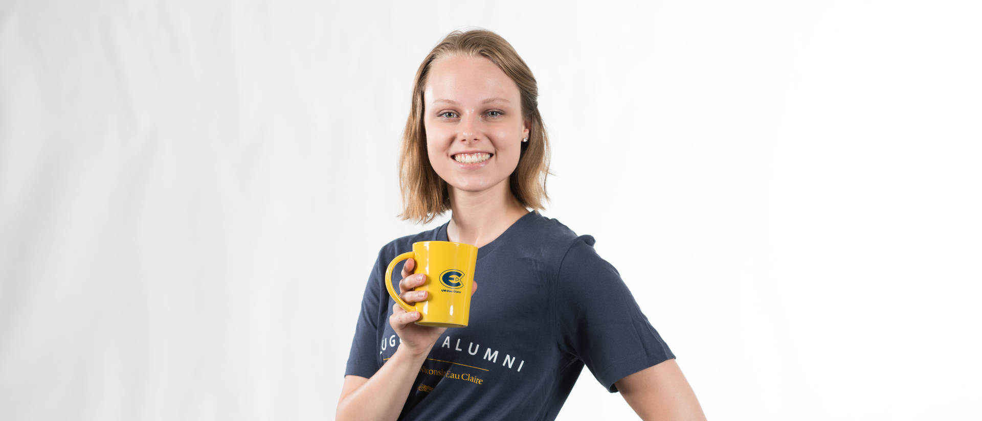 Alumni shows off blugold apparel and mug
