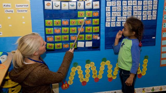 Student teaching an elementary child numbers