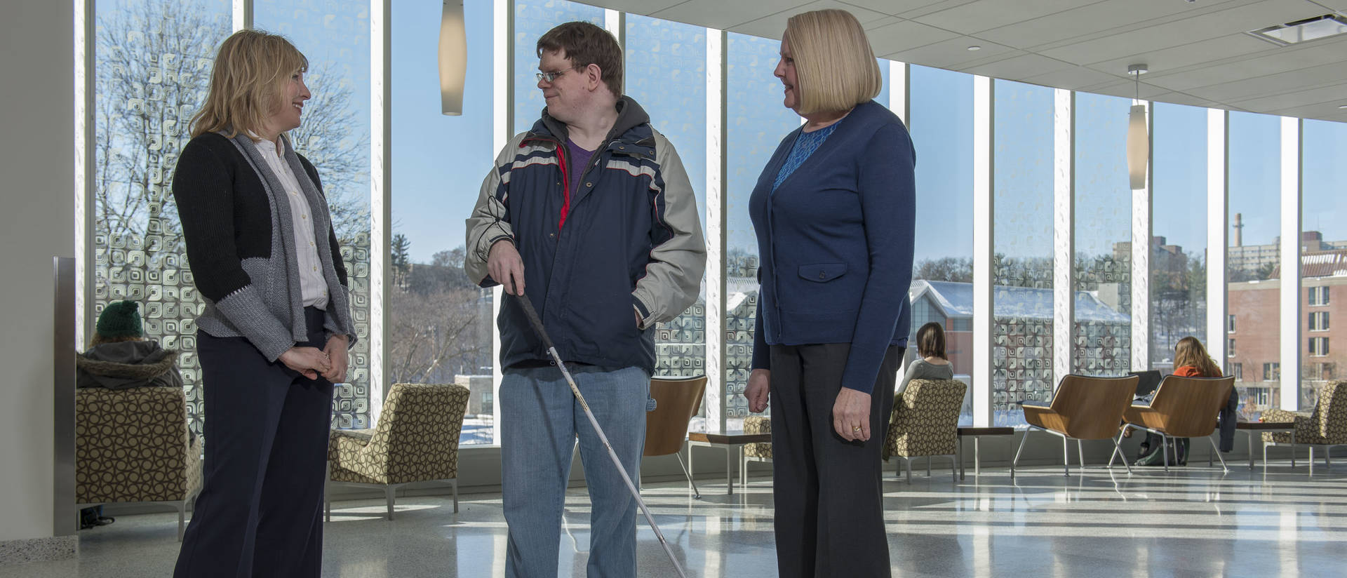 Student with visual aid cane and SSD staff in Centennial Hall atrium