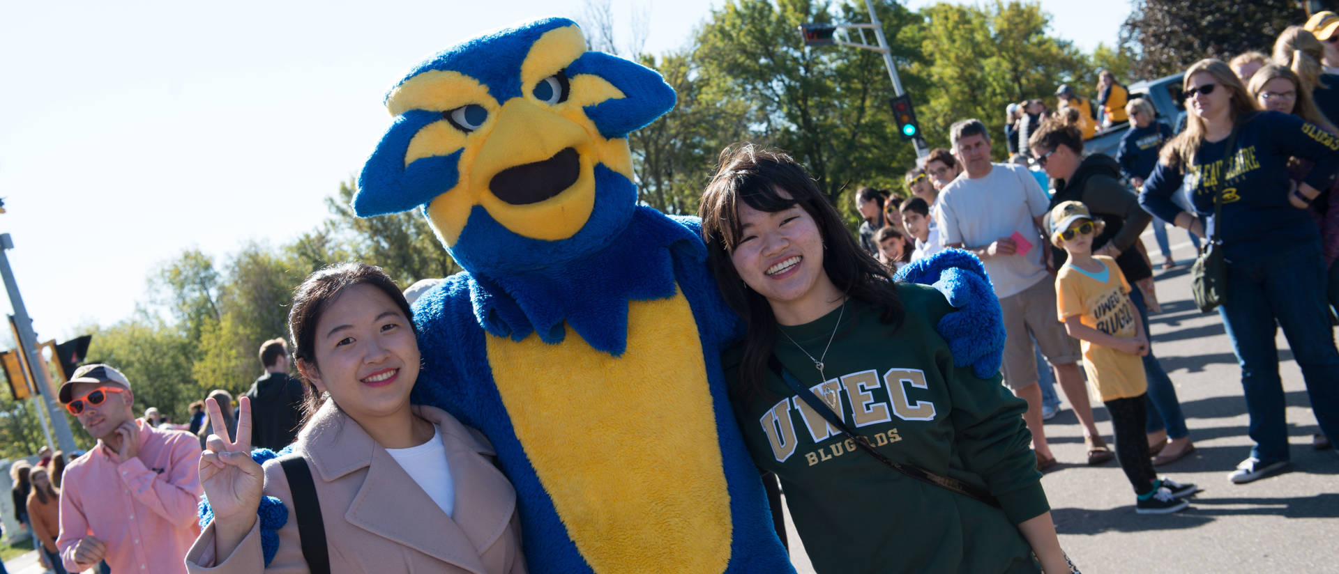 Blu the mascot poses with students at the 2017 Homecoming Parade