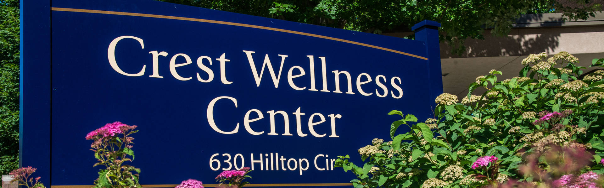 Crest Wellness Center sign surrounded by flowers